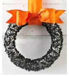 "Classy, creepy and cheap - the three ""C""s of crafting. Plain, dollar store styrofoam wreath, hit.glue plastic spiders, add ribbon. Viola!"