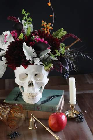 I love this! Grab a foam skull or even ceramic from a craft store and use it as a vase. Pick the flowers, choose adornments like bats or ghosts on a stick, and make an elegant,  yet eerie, centerpiece or accent.